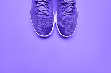 Purple running shoes on purple background to run for weight loss