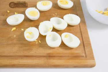 scooping out yolk from hard-boiled eggs