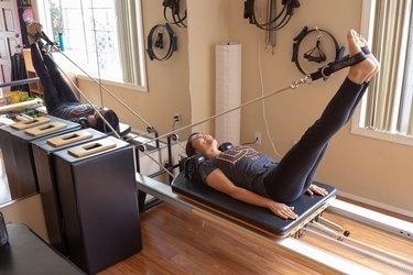 Kristina stretches on her Pilates Reformer.