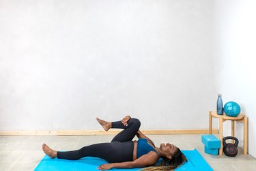 woman doing a supine knee-to-chest stretch