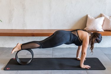 woman doing Plank Pose (Phalakasana) with a yoga wheel