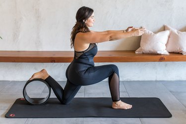 woman doing Low Lunge (Anjaneyasana) with a yoga wheel