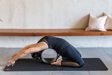 woman doing Pigeon Pose (Kapotasana) with a yoga wheel