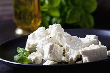 Feta cheese and basil leaves on black plate