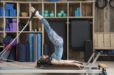 Woman trying out reformer Pilates — one of the types of Pilates