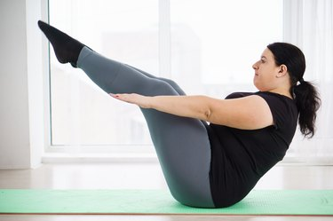 Woman doing Pilates workout to tone her abs