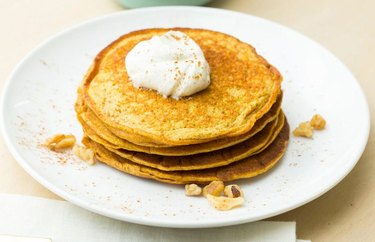 A white plate with a stack of pumpkin pie-flavored pancakes, topped with walnuts and whipped cream