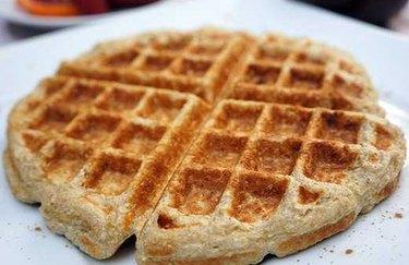 Cinnamon roll waffle on white plate.