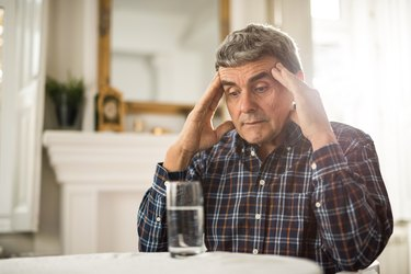 An older man sitting at a table with a glass of water, with his hands on his temples because he is feeling dizzy
