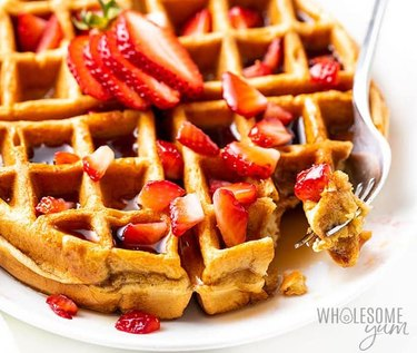 Low-carb Belgian waffle topped with sliced strawberries and syrup.