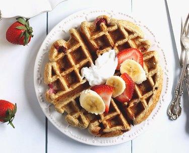 Greek yogurt Belgian waffle topped with cream, bananas and berries.