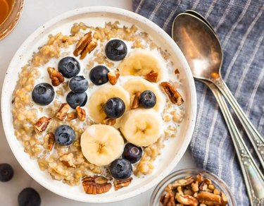 Bowl of oatmeal topped with milk, blueberries, pecans and banana slices.