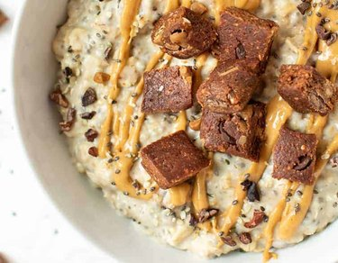 A bowl of oats topped with drizzled nut butter and a chopped up protein bar.