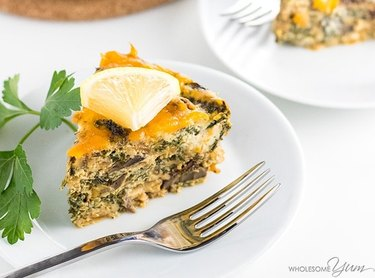 Slice of kale and mushroom egg casserole on a plate topped with a lemon wedge.