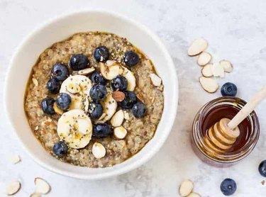 Bowl of quinoa and oat porridge topped with honey, seeds, sliced bananas, blueberries and sliced almonds.