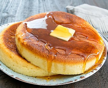 Two Instant Pot pancakes on a plate topped with butter and syrup.