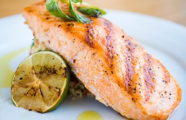 A filet of grilled salmon served with grilled lime and rice