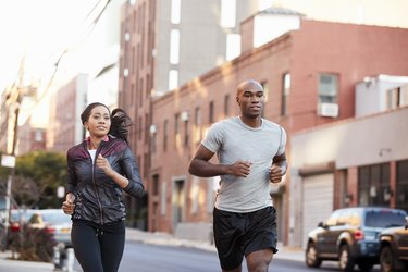 Young couple jogging in Brooklyn street, close up