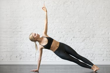 Young woman in side plank pose, studio background