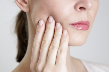 Close up of a women working her jaw.