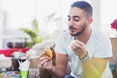 man eating burger off the Whatabuger menu