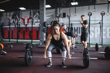 Strong female weightlifter preparing to do a deadlift