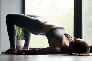 Young sporty woman doing Glute Bridge exercise
