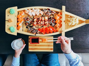 Man eating sushi from a sushi boat in Japanese restaurant, directly above personal perspective view