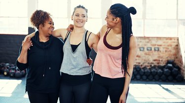 Three women friends walking arm-in-arm after an exercise class