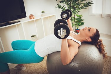 woman exercising With Dumbbells and stability ball At Home