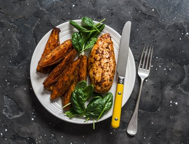 Baked chicken breast with sweet potatoes and spinach on a dark background, top view. Balanced healthy lunch