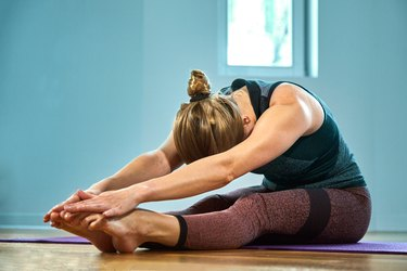 Young sporty woman practicing yoga, working out, wearing sportswear, pants and top, indoor close up, yoga studio