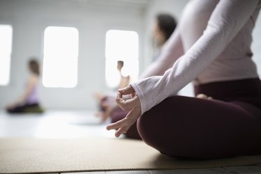 Close up woman practicing lotus position meditation with hand in gyan mudra in yoga class