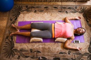 Overhead view of woman lying down meditating