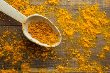 Turmeric powder in wooden spoon on wooden rustic looking table
