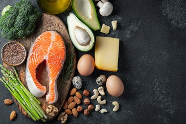 A set of healthy food for keto diet on a dark background. Fresh raw salmon steak with flax seeds, broccoli, avocado, chicken eggs, nuts and asparagus on a wooden Board. Top view with copy space