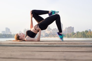 Fitness girl doing butt-sculpting exercises during training workout outdoor