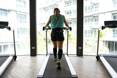 Asian woman walking on treadmill with building in background