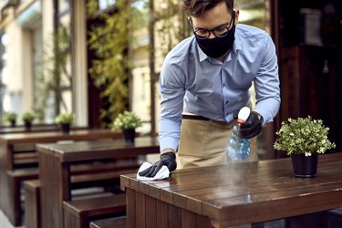 photo of restaurant server wearing face mask and sanitizing wooden table outside
