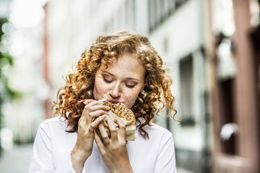 Portrait of young woman eating bagel outdoors on a refeed day