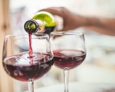 Hand pouring red wine in glasses