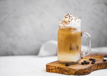 Ice coffee cup with cream. Ice frappuccino summer refreshing coffee drink with cream