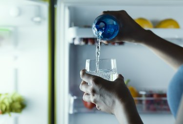 Woman taking a bottle of water from the fridge and pouring it into a glass
