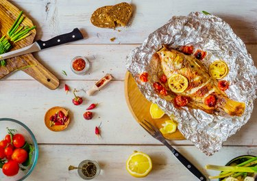 Table setting  with different dishes and grilled fish