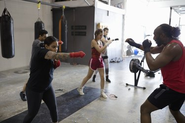 Instructor leading boxing class in gym