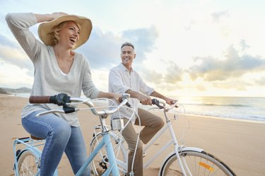 Mature couple cycling on the beach at sunset on vacation
