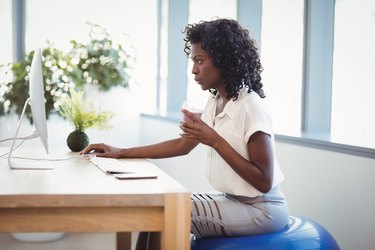Executive sitting on fitness ball while working at desk