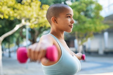 Woman using small weights to do shoulder exercises