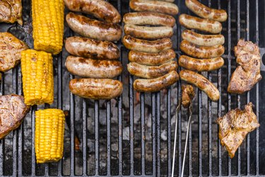 Different meat, maize and fried sausages on barbecue grill