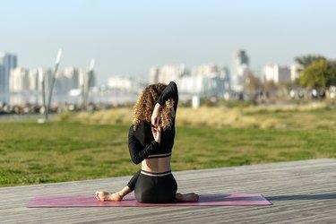 Woman doing yoga exercise away from city life. Gomukhasana. Cow face pose.